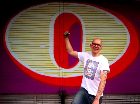 Ben Eine davanti ad un suo graffiti dipinto in Middlesex St. a Londra nel 2010